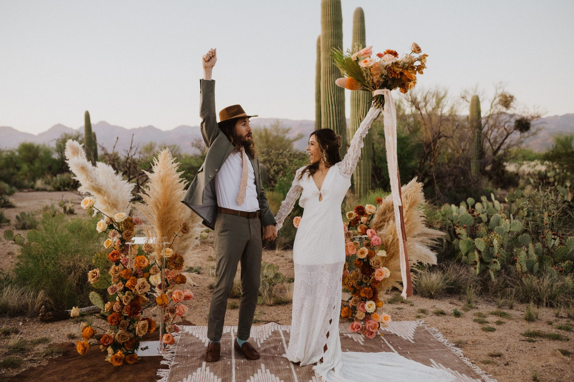 bride and groom jump with excitement as they get married in a bohemian wedding in saguaro national park